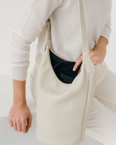 The perfect bucket bag, in supple natural milled leather. Two interior pockets hold your phone or other essentials. Top zipper closure. Adjustable shoulder strap. Fully lined.