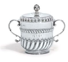A WILLIAM AND MARY SILVER PORRINGER AND COVER LONDON, 1691, MAKER'S MARK SL MONOGRAM Cylindrical on spreading foot, the lower body part spiral-fluted below a gadrooned band, the detachable cover with a broad gadrooned border and a foliage finial, with scroll handles, the side and base each engraved with initials,