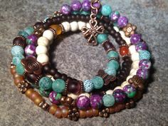 Many kinds of beads on this one… matte brown and transparent topaz glass beads, green frosted fire agate, howlite turquoise white, purple glass beads and rain stone beads in purple and green. Plus a lot of cute spacer beads and charms in copper/copper color to add such personality to this piece! Finished off with a cross charm.  $35