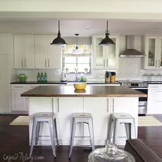 Kitchen Renovation - love the white cabinets & subway tiles, dark countertops, island w/ stools, dark lighting, and no-sew Roman shade.