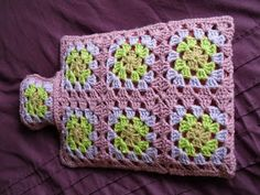 Made with 14 granny squares, crochet 8 together first (2 x 4) and then 4 together (2 x 2) to make a flap at the back and use 4 little pink buttons to close it to get the water bottle in and out to wash the cover, leave top open to fill with hot water without removing the cover.