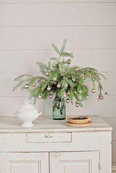 Christmas can be creative. Foliage in a vase of water with Christmas Ornaments is just delightful.