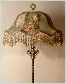 Beautiful ornate1920s hand-painted antique lamp base holds a stately and elegant Chateau shade in soft tones of dusty green, pewter, and antique pink and peach. Covered in antique silk damask, silver and gold metallic lace, the front is adorned with trailing antique silk ribbon roses from Europe. Double layer beaded fringe adorns the bottom of the shade. A jeweled pull chain turns on the lamp.
