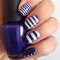 Blue striped button themed nail art design. Dark blue and white polish is used on this design for the stripes with gold beads on top for the button details.