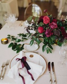 Napkins were tied with burgundy ribbon, and affixed with tags calligraphed with each guest's name. The menus were adorned with a gold wax seal, echoing the gold rim of the plates. Photo: @mistermoes + event planning & design, floral design: @thenouveauromantics.