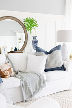 White slipcovered sofa | Large mirror living room | All white décor | Cozy décor ideas