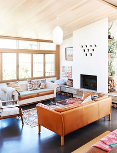 Mid-century living space with modern light fixture, fireplace, and leather sofas