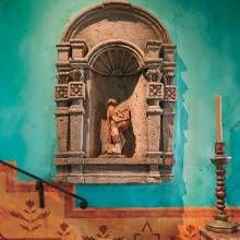 An antique stone niche in a hallway holds a carved statue of San Jose of Guatemala.