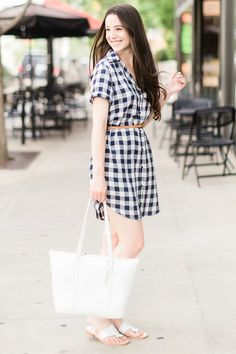 This preppy plaid shirtdress outfit features a navy BB Dakota Cicily Shirtdress styled with white Jack Rogers sandals, a white Vera Bradley Mallory Tote, skinny braided leather belt, and large pearl stud earrings. Click through for the full casual summer outfit idea by southern fashion blogger Stephanie Ziajka from Diary of a Debutante! #summerstyle #affordablefashion #bbdakota #jackrogers #verabradley #preppy
