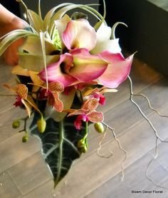 Custom, unique bridal bouquet with pink calla lilies, dendrobium orchids, tillandsia (air plant), alocasia leaf and curly willow.