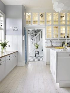 glass cabinets, my fav tile backsplash, white cabinets. love the subtle striped wallpaper and blue door