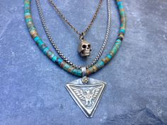 Multi-layered necklace: bronze skull, silver eagle, mixed metal, turquoise.