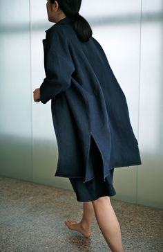 Coat and dress of tightly woven linen. The coat's edges are sewn by hand and it has little metal weights | Jurgen Lehl for Babghuri