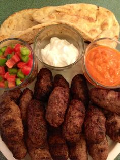 """""""Cevapi with Ajvar, Yogurt & Shopska Salata"""". Cevapi are a mixture of beef and lamb mixed with simple seasonings that don't overpower the flavors of the meats. Ajvar is a puree of roasted eggplant and red bell peppers, with garlic, lemon, parsley and other spices. The chopped shopska salad is made with 4 fresh Roma tomatoes and 2 green bell peppers. Bosnian Food, Bosnian Recipes, Grilled Lamb Chops, Grilled Meat, Shopska Salad, Parsley Salad, How To Make Sausage, Roma Tomatoes, Middle Eastern Recipes"""