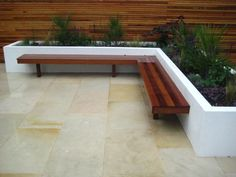 Modern garden with neutral paving patio area, white planting area and a nice custom built bench. Garden completed by our member Oasis Landscapes, see more of their great work here - https://www.experttrades.com/trade/oasis-landscapes/gallery  #garden #plants #bench #patio #paving #home #inspiration #gardenideas #gardendesigns