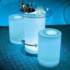 Color-Changing LED lighting gives this table a chic, after-hours glow.... poolside tables....great night pool party idea!