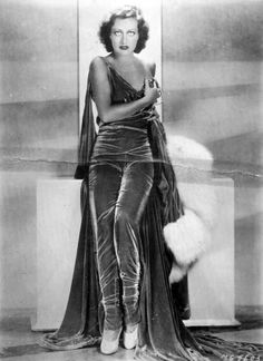 Joan Crawford, wearing the pants, if velvet pants...  Photographed by George Hurrell, 1930.