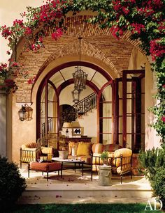 The loggia of a Los Angeles villa decorated by Mark Boone serves as an outdoor living room. Vaulted ceilings, archways, and hanging lanterns extend from the entrance hall to the adjoining alfresco area, creating a seamless flow between inside and out. (May 2006)
