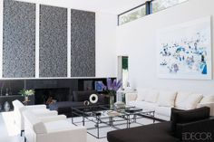 In the living room of a modernist home in Geneva, Alexandra de Garidel-Thoron hung artworks by Rafael Lozano-Hemmer and a photograph by Massimo Vitali; the cocktail tables are by Philippe Berry, the armchairs are by Christian Liaigre, the sofa is by Promemoria, and the floor is painted concrete.   - ELLEDecor.com