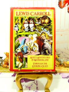 Lovely Vintage Book Alices Adventures in Wonderland and Through the Looking Glass both stories in one omnibus edition. Prettily bound in Red Cloth embossed with a gilt embossed image of Alice and a colourful Dust Jacket. Nice to have both stories combined together in the one book.