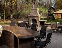 Outdoor patio features stained concrete bar and brick fireplace
