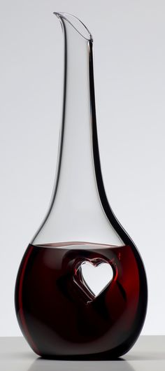 A labor of love, the Black Tie Bliss decanter displays a rotund foundation with an off-center heart stamped from each side, thus compressing the crystal into a thin pane of solid glass. This innovative design forces the wine to pool around the element while providing a place for the fingers to rest as the wine flows out of the decanter into a waiting glass.