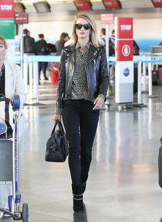 Rosie Huntington-Whiteley wears a leopard-print button-down shirt, leather jacket, skinny jeans, suede chain boots, and a black duffle bag