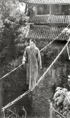 A budist monk crossing a bridge made of two chains, in China