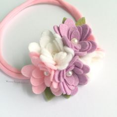 A fun, soft, and feminine pastel felt flower headband for you or your little wild and free flower child!This listing is for one pink, purple, and white clusterflower band. Each band includes one cluster of six handmade mini rosettes among a sprinkle of woodland green leaves in varying shades of green.  These flower and leaf arrangements are attached to an amazing nylon band that is extremely soft, stretchy, non-marking and it does not leave a dent! The band will stretch to accommodate your…