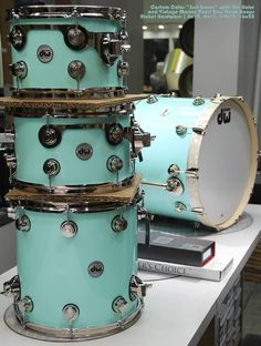 "Drum Workshop set in custom color ""Surf Green"" with lite flake and vintage marine pearl bass drum hoops and nickel hardware. Sizes 8x12, 8x13, 14x14. 16x22. Smooth."