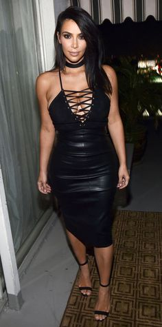 Kim Kardashian West in a sexy black plunging lace-up bodysuit that she styled with a body-hugging black leather midi skirt, a '90s-style choker, and black sandals.