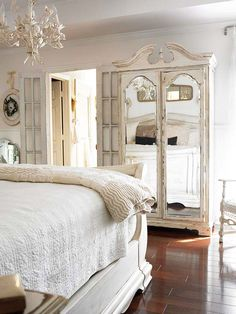 Decorating with Summer Whites: This Queen Anne-style armoire wore a dark finish until a few layers of paint and a bit of sanding gave it a distressed look that suits this all-white bedroom. Layer different shades of white to provide more texture and a sense of age to a room. Even an old metal chandelier found new life thanks to white paint.