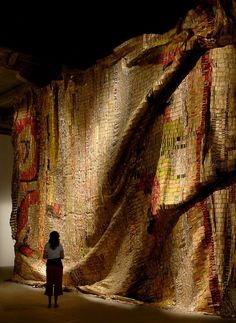 El Anatsui; Ghanian artist who uses found detritus such as bottle tops and electrical wire and flattens it and ties it together to create a woven textile.