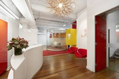 """In keeping with the name of their company, Red Rock Consulting's Sydney office includes heavy use of fire-truck red in their aesthetic. Created by Rolf Ockert Design, the workspace is so vibrant that the company named their main meeting room the """"WTF?"""" room, due to the exclamations uttered by staff and clients on first entering the space. It features trippy wavy red walls. 60s-inspired egg chairs and a curved corner sofa, so their reaction is hardly suprising!"""