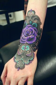 A delicately shaded purple color rose tattoo sits on the wrist .