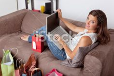 Woman sitting with laptop and shopping bags Royalty Free Stock Photo