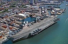 Ministry of Defence computer generated image of how a controversial future giant aircraft carrier would look in its home base was unveiled today by the Royal Navy. It shows one of the carriers alongside at Portsmouth Naval Base, Hampshire, where it would take up three jetties