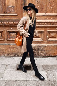 5 Cool Ways To Style A Cardigan This Season: Fashion blogger 'Mija Flatau' wearing a camel long cardigan, a black t-shirt, black skinny jeans, black booties, a black hat, a brown bucket bag and black sunglasses.