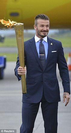 It's arrived: David Beckham looks pleased as he carries the Olympic torch at RNAS Culdrose this evening 18 May 2012