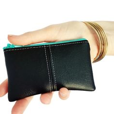 This black small change purse features vegan leather and is the ideal coin pouch for your handbag.  The ESSENTIAL coin purse might just be the last coin purse you ever buy. Made in sumptuous vegan leather, the exterior has a designer feel yet is water resistant and durable. Inside, a bold cotton print holds your coins, cash and cards securely. You can also use it for lip balm, mints, ear buds, or any other small items that stray to the bottom of your bag.  Materials: vegan leather (faux…