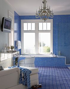 Bright royal blue glass tiles and the clear-glass wallcovering are meant to suggest the ocean and the foam on the surface of breaking waves.