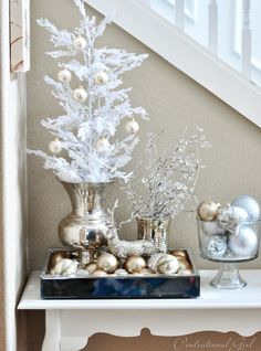 Silver and white table vignette with trees, tray of ornaments and bowl of ornaments
