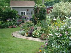right side of back yard. Perennial and annual flower beds, walking path in front leads to arbor seat.