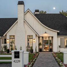 Charm = White farmhouse at night with sweeping roofline and beautiful paver stone walkway. White Farmhouse Exterior, White Exterior Houses, Country Farmhouse Decor, Modern Farmhouse Style, Custom Home Builders, Custom Homes, Mountain Home Exterior, Holland House, Tudor Style