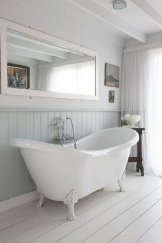 Make your small Victorian bathroom appear light and bright with white washed floorboards, a slipper bath and white flowing drapes... #Victorianbathrooms #bathrooms #bathroomsideas #traditionalbathrooms