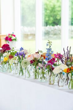 colorful, yet simple floral display using vintage bottles of all shapes and sizes with a variety of blooms