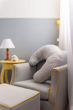 Detalhes da decoração de quarto de bebê amarelo e azul, cadeira de amamentação cinza com detalhes amarelos.