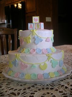 Buttons Baby Shower Cake - BC icing w/fondant buttons and baby clothes. Purchased block on top. My creation, inspired by a Wilton cake. Note: this cake was before I learned how to smooth buttercream.  Just sayin'!!