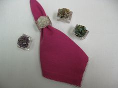 Napkin rings from Left to Right: Purple Shell, Clear Ice Shell, Cobblestone Shell and New Water Shell Napkin-CW Fuchsia/White Picot Edge