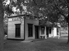 """Montras (vitrines). A réplica construída em 1960, é exemplo de negócios mercantis localizados em uma cidade do condado de Middlesex, província de Ontário, Canadá, entre 1910-1920. As """"vitrines"""" em Fanshawe Pioneer Village representam um dos projetos especiais do curador fundador Wilfrid Jury e destinaram-se a exibir impressionantes coleções de artefatos da época."""